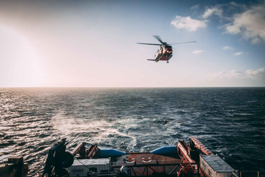 A helicopter flies above a container ship with someone dangled from it. Photo by Oliver Paaske on Unsplash.